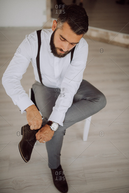 Groom putting dress shoes on