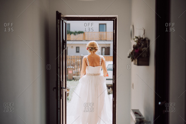 Rear view of bride walking out door