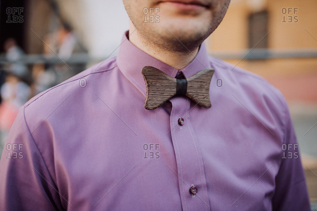 Man wearing purple shirt and wooden bowtie