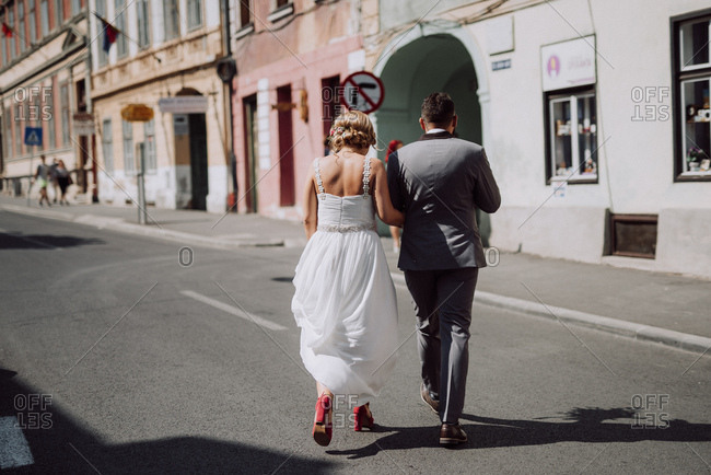 Rear view of bride and groom walking across a street