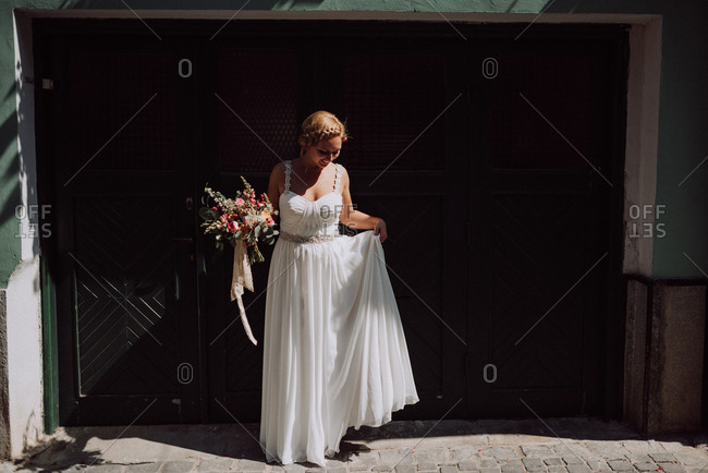 Bride standing on sidewalk holding bouquet