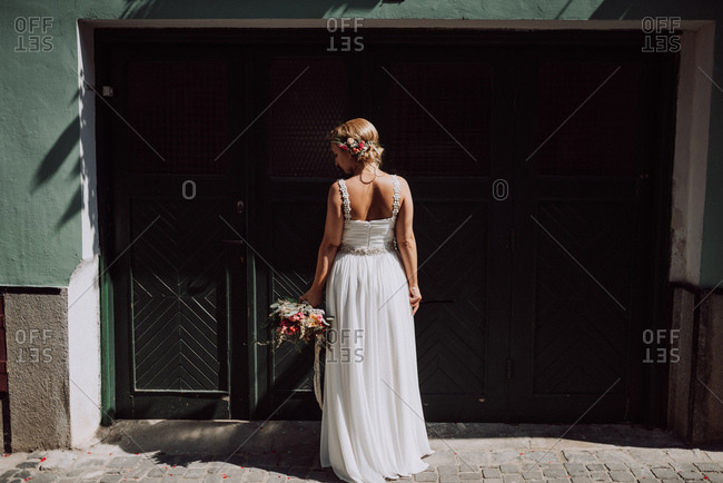 Rear view of bride standing on sidewalk holding bouquet