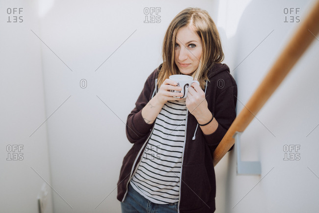 Woman standing on stairs enjoying cup of coffee