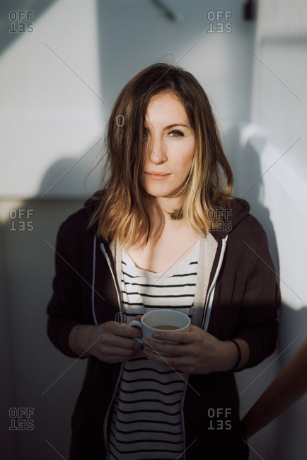 Portrait of a woman standing on stairs drinking cup of coffee
