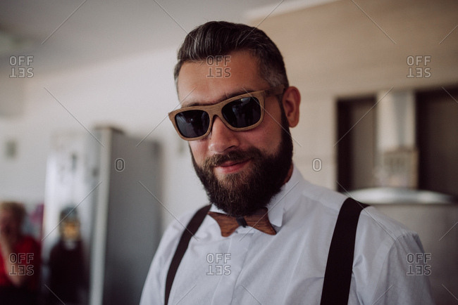 Portrait of a groom wearing wooden sunglasses and bowtie