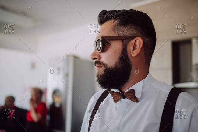 Groom wearing wooden sunglasses and bowtie