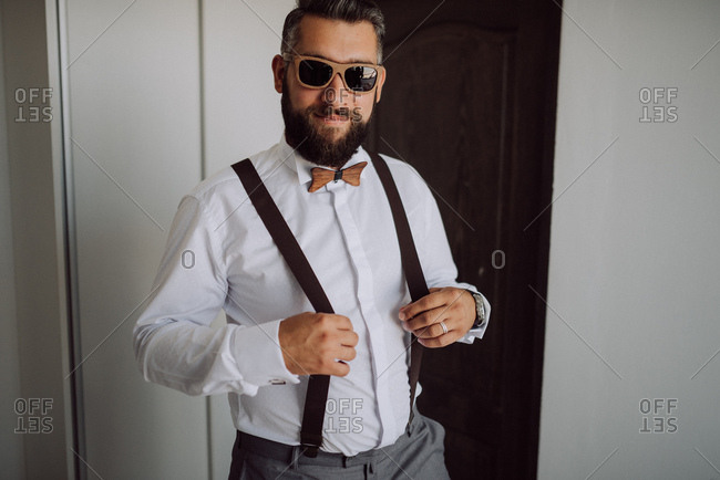 Happy groom wearing suspenders and wooden sunglasses with a bowtie