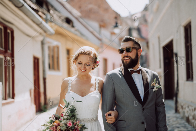 Smiling bride and groom walking a city street