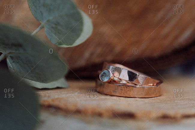 Close up of wedding rings on a wooden stump
