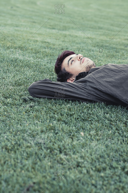 Young man lying on lawn