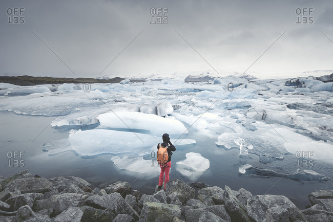 Iceland- view of Joekulsarlon- glacial river lagoon with man standing in the foreground