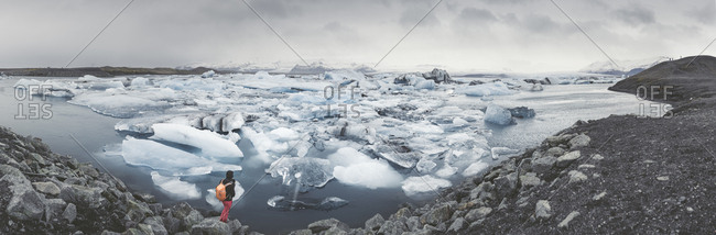 Iceland- panoramic view of Joekulsarlon- glacial river lagoon with man standing in the foreground