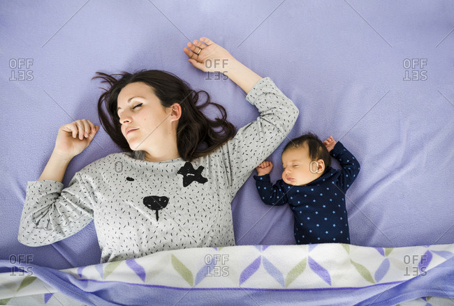 Newborn baby girl and mother sleeping in bed