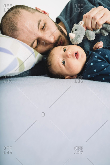 Father playing with his newborn baby girl and a  cuddly toy on bed