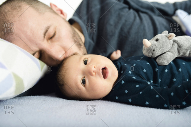 Father kissing his newborn baby girl on bed