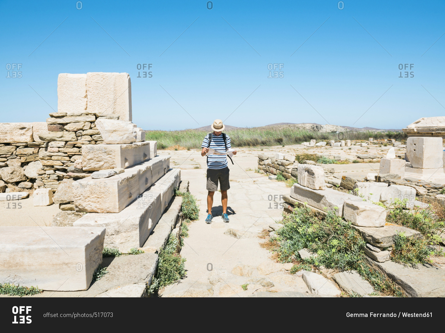 Greece Mykonos Delos tourist looking at map at archaeological