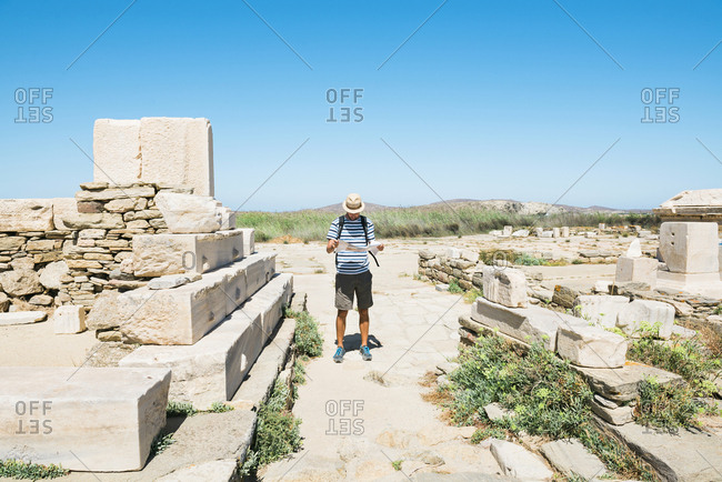 Greece- Mykonos- Delos- tourist looking at map at archaeological site