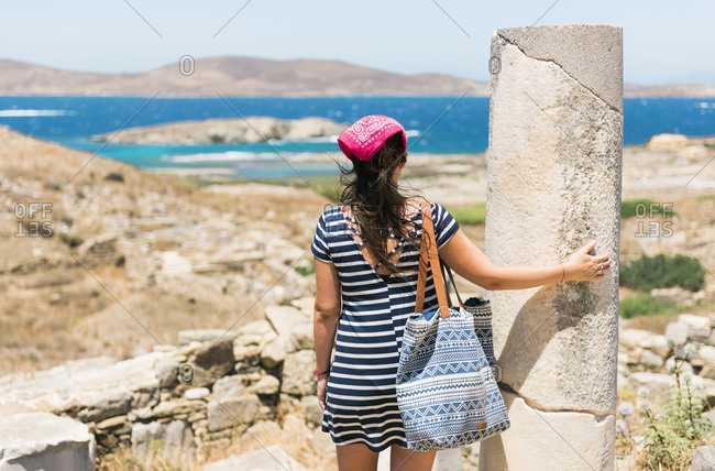 Greece- Mykonos- Delos- tourist at archaeological site enjoying the view