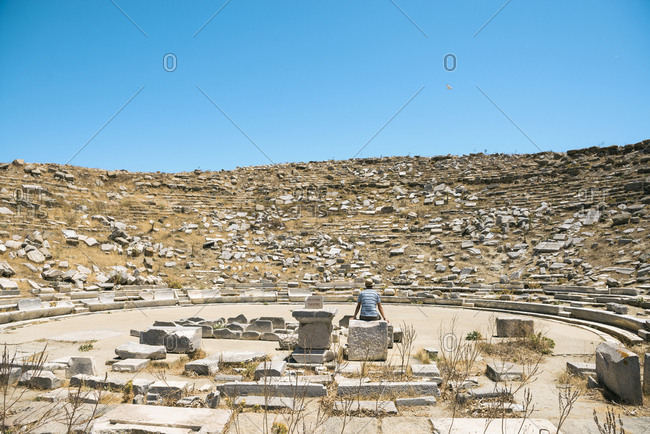 Greece- Mykonos- Delos- tourist visiting the Theatre