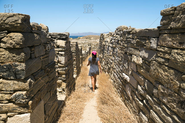 Greece- Mykonos- Delos- woman walking along the old houses at archaeological site