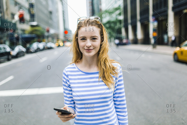USA- New York- Manhattan- Young woman walking in the street- holding mobile phone