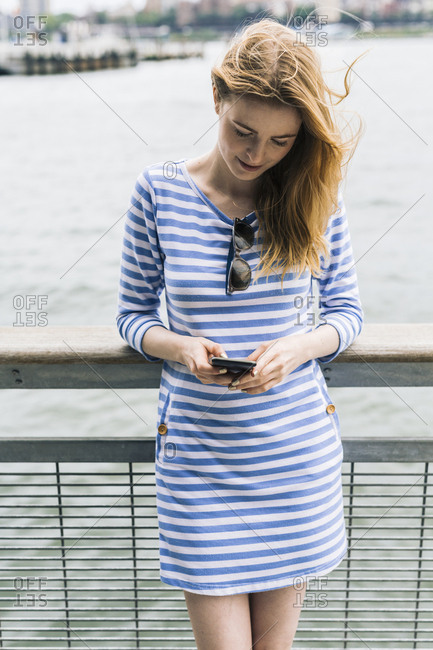 USA- New York City- Young woman standing in Manhattan using smart phone