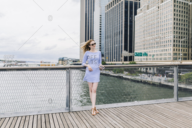 USA- New York City- Young woman standing in Manhattan at railing- holding smart phone