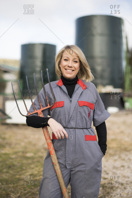 Woman working on farm- holding hay fork