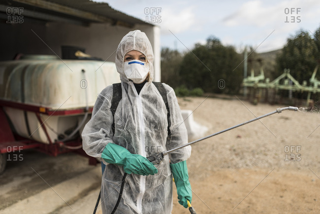 Woman wearing protective overall to fumigate olive trees