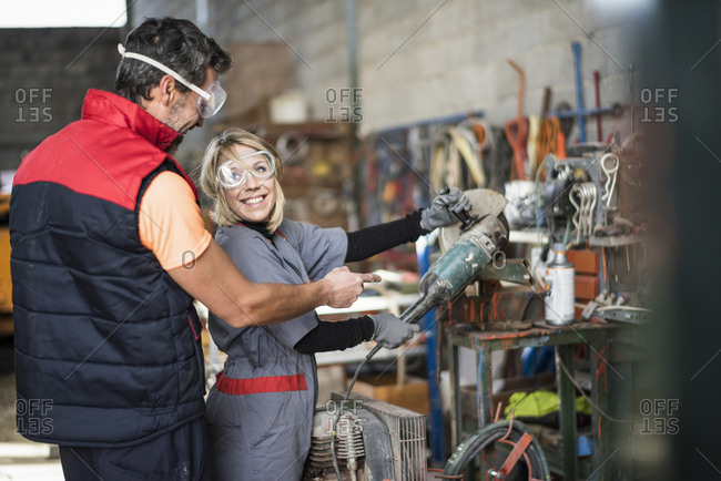Man helping woman how to use buzz saw