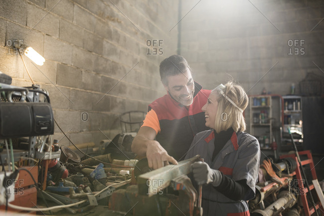 Couple working in farm workshop- using bench vice