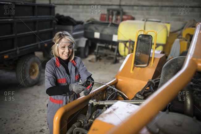Woman cleaning farm machine