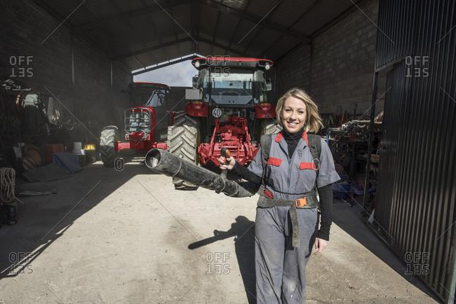Woman in farm garage carrying air blower