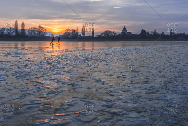 Germany- two ice skaters on frozen Lake Constance with Reichenau Island in the background at sunset