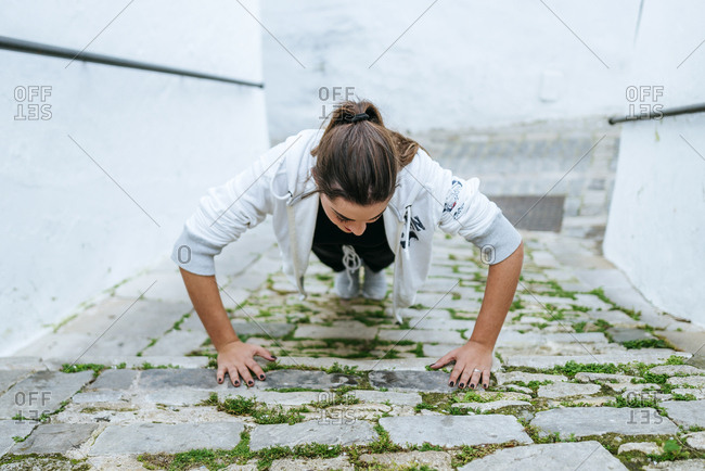 Young woman doing push ups in the street