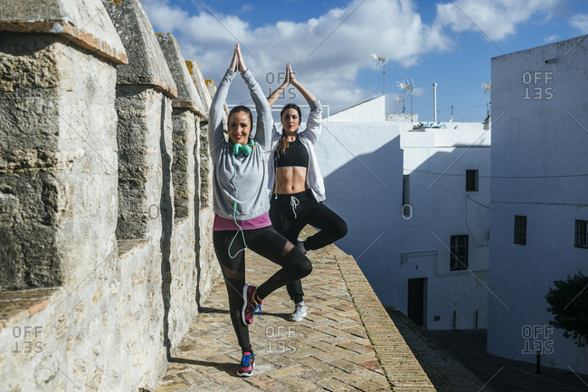 Two young women exercising yoga in the street