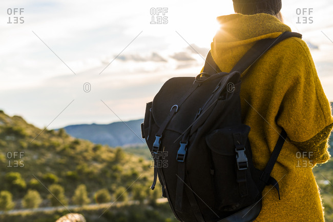 Young woman with backpack in nature at sunset