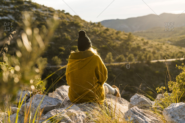 Young woman sitting on rock in nature looking at view