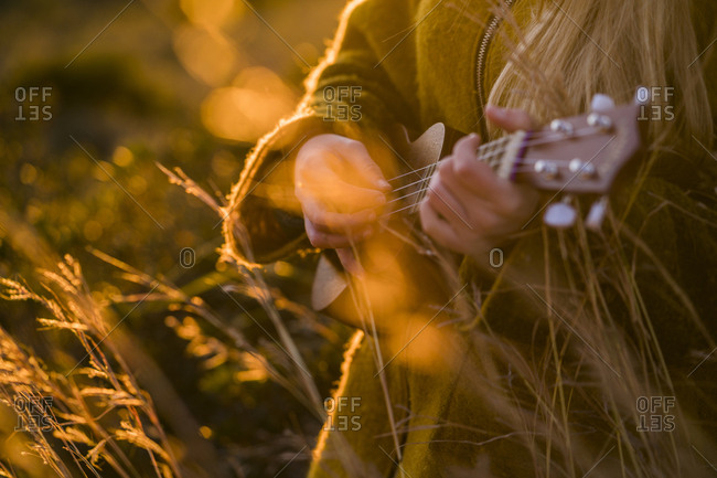 Close-up of woman playing ukulele in nature