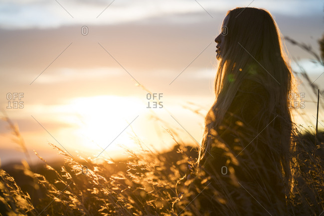 Young woman in nature at sunset