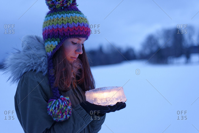 Teenage girl holding cake made of ice with candle inside
