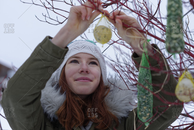 Portrait of smiling teenage girl hanging up fat balls in winter
