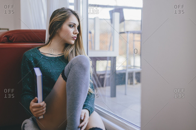 Young woman with book sitting on the floor of living room looking through balcony door