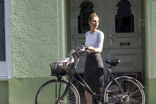 Young woman with Dutch roadster standing in front of house entrance