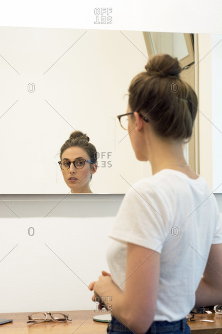 Young woman testing glasses frames in an optician shop