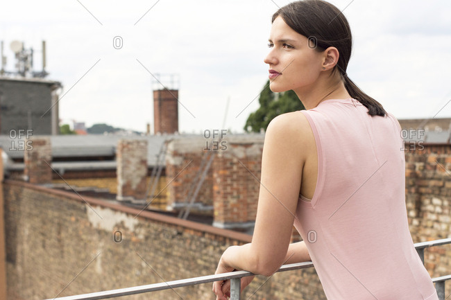 Young woman leaning on railing of roof terrace