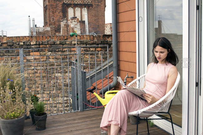 Young woman reading newspaper on roof terrace