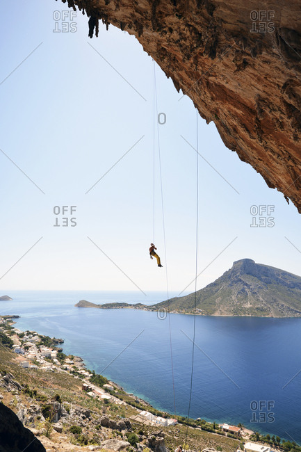 Greece- Kalymnos- climber abseiling in rock wall