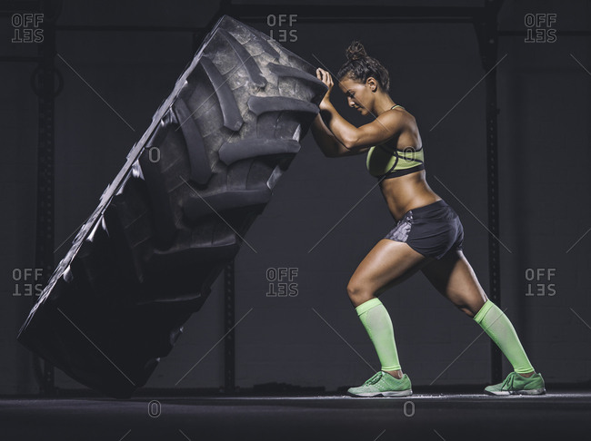 Young woman lifting up a tractor tire