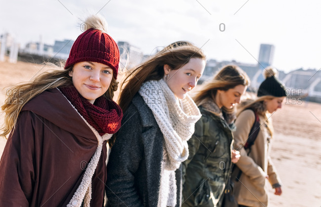 Portrait of teenage girl walking on the beach with her friends in winter